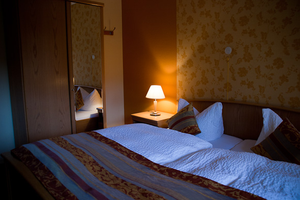 Bett, Lampe und Schrank in angenehm warmen Farben