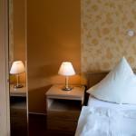 Nachttischlampe neben einem Bett, spiegelt sich im Wandschrank-Spiegel