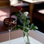 Windkerze neben einer Rose