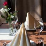 auf dem Tisch: Teller, Weingläser, Servietten, Rosen
