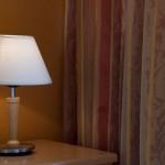 Nahaufnahme einer Nachttischlampe vor einem Vorhang